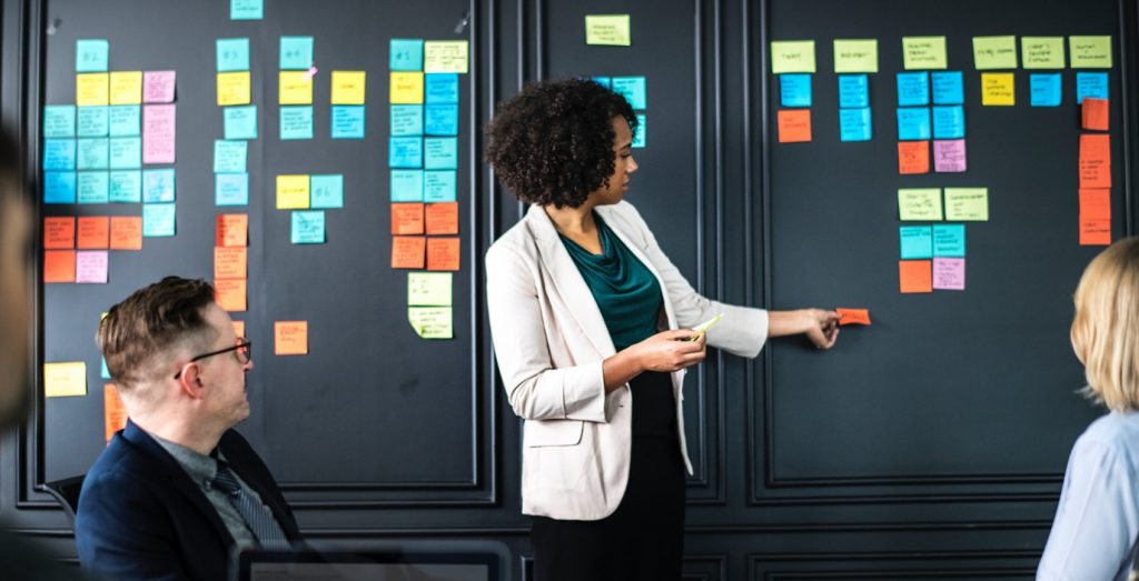 A person standing in front of a whiteboard moving a post it note in a team meeting